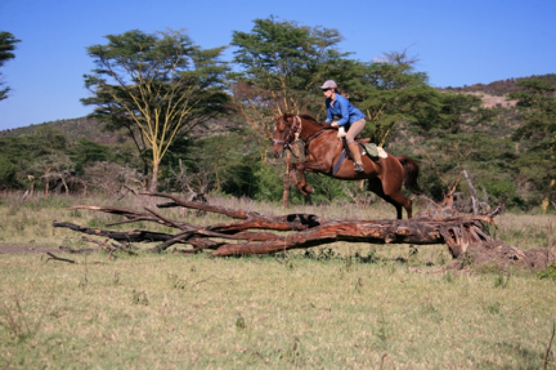 Alice jumping over a tree on her horse riding safari holiday