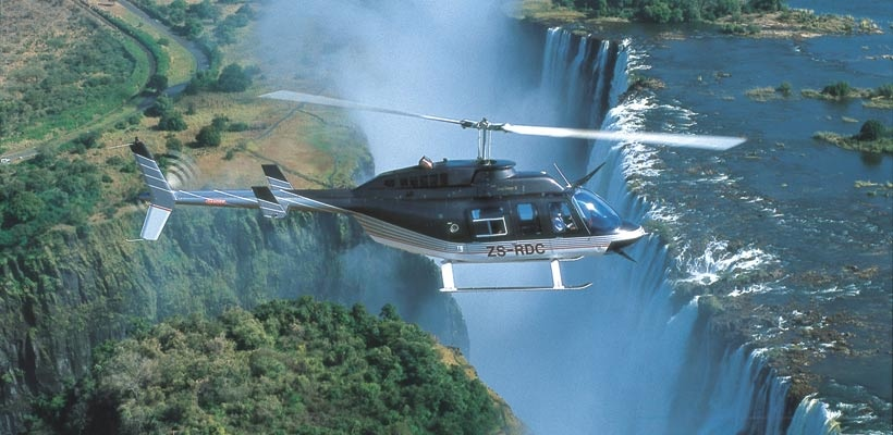 a helicopter hovering over vic falls
