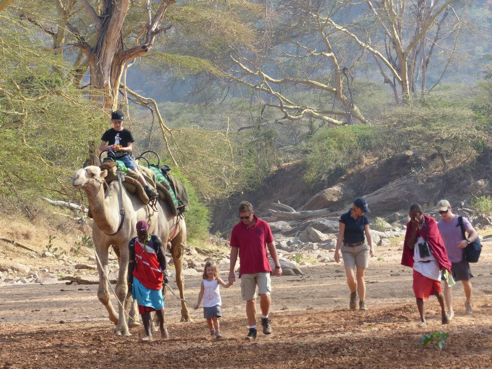 a family on a walking safari with a camel