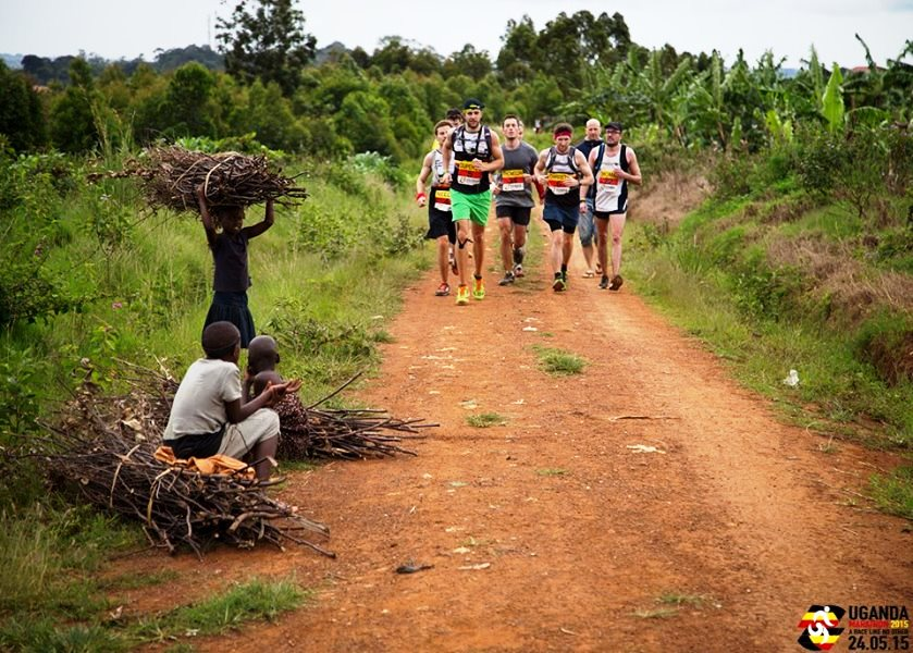 Uganda Marathon runners and children with firewood, photographer Peter Wilson