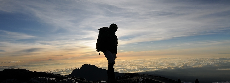 At sunset hiker at the summit of Mount Kilimanjaro