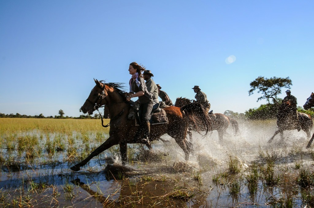 Women and guides galloping through water, African Horseback Safaris, Botswana