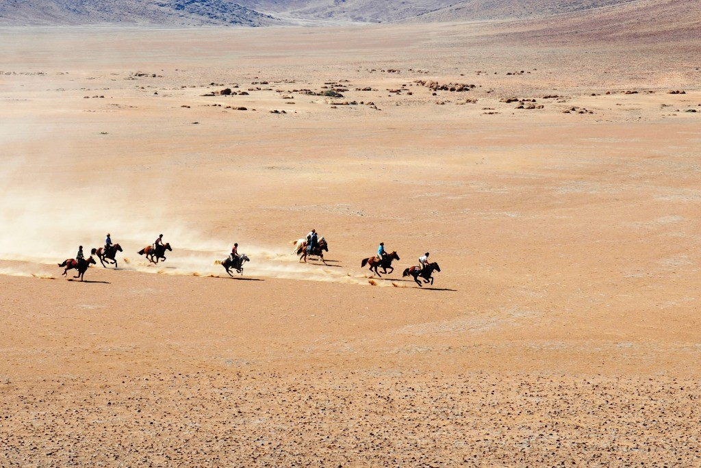 group of riders gallop on the flat Namibian plains