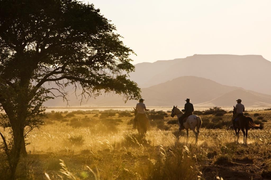 riders in the sunshine Desert Homestead, Sossusvlei, Namibia