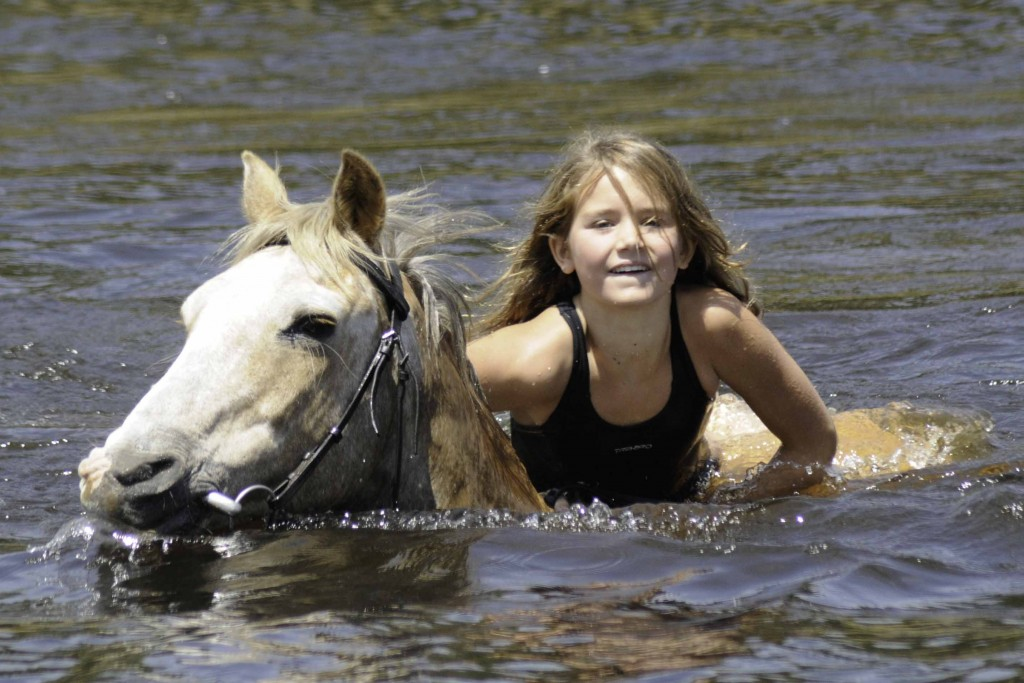 Girl swimming with grey horse, Horizon Horseback, Waterburg, South Africa