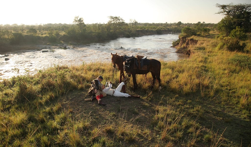 A romantic couple by the river with their horses, Safaris Unlimited Kenya