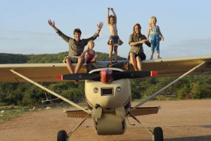 Saba and family sitting on husband Frank's plane at Elephant Watch Camp front of plane