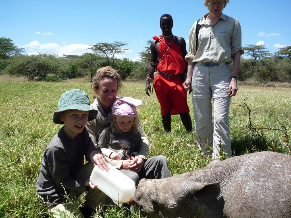 children and parent bottle feeding a baby rhino