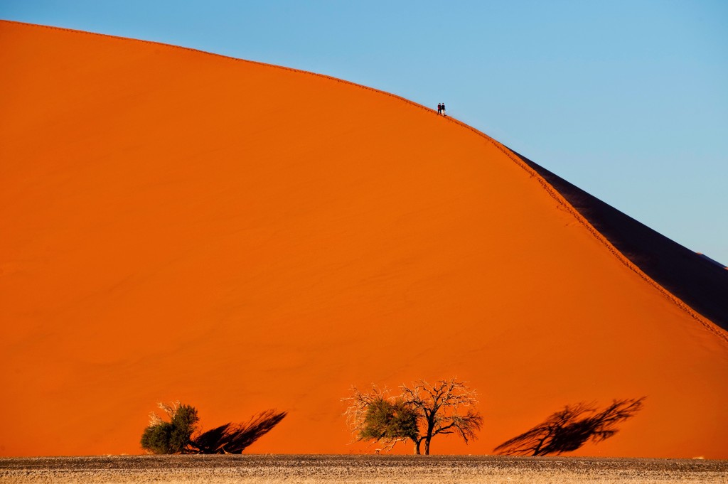 Magnificent red dunes and people climbing at Sossusvlei. Image Kulala Camp, Namibia