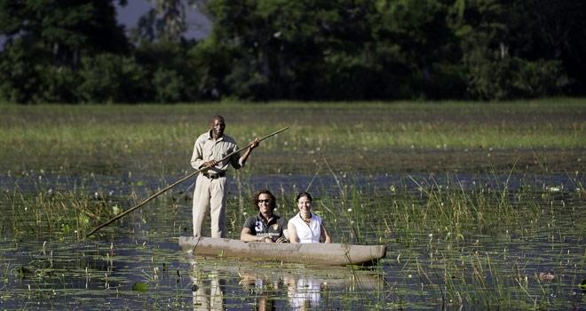 Botswana safari - couple in a mokoro with safari guide