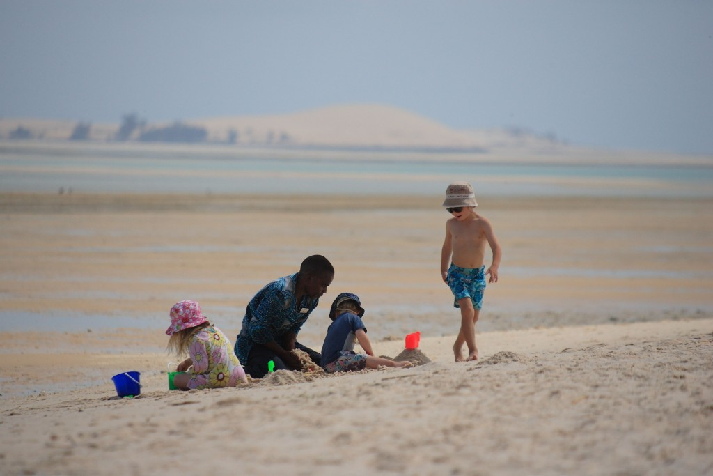 Children and sitter playing on the beaches at Azura, Benguerra, Mozambique