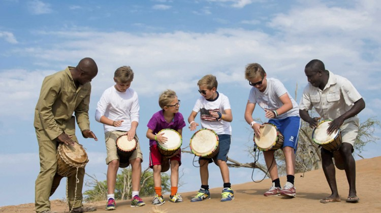 Male teenagers drumming with male guides a Little Kulala Namibia Wilderness Safaris