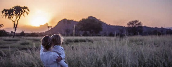 Mother and child watching the sunset on safari in Africa on a family safari