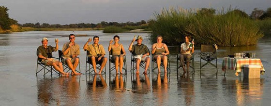 Group travel - travellers sitting on chairs in the river with sundowner drinks in a row