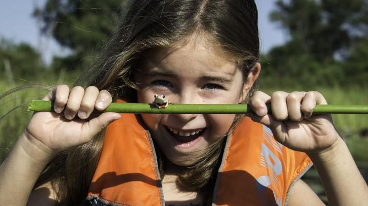 Botswana family safari - girl canoeing in the Delta on safari with a frog