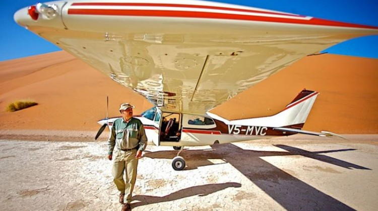 Schoeman brothers Namibia air safaris, guide walking towards you under bush plane wing in Namibia desert