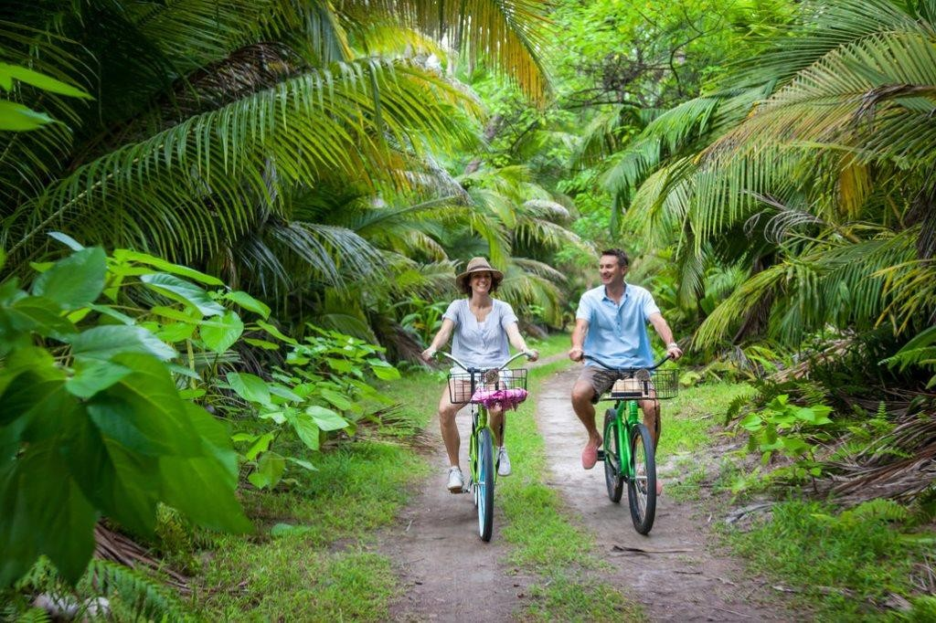 romantic couple on mountain bikes Desroches Island, Seychelles