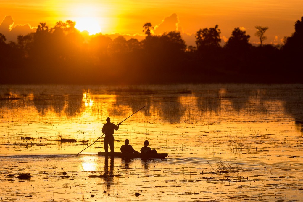 Mokoro boating at sunset, Pelo Camp Okavango Delta, Botswana