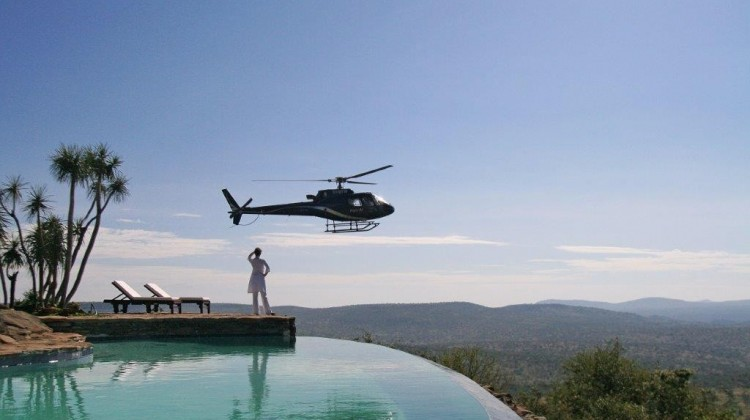Heli safari at Loisaba, Kenya - lady by infinity pool with helicopter
