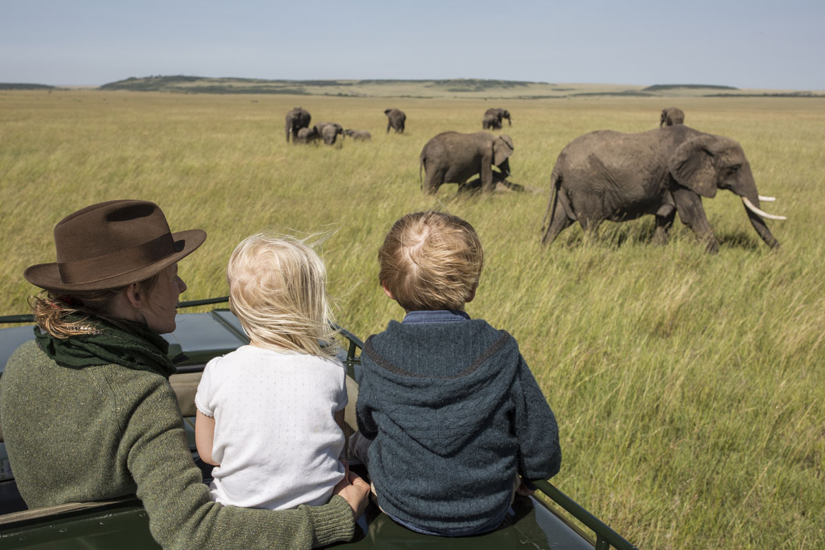 Rekero Camp children viewing elephants from safari drive Masai Mara, Kenya