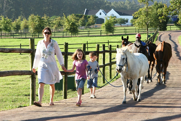 A family and guide walk the horses at Kurland, Garden Route, South Africa