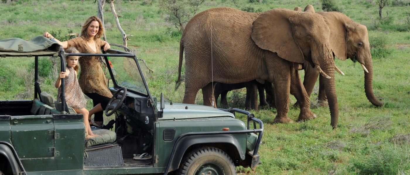 Saba Doulgas Hamilton with daughter in safari vehicle with elephant herd