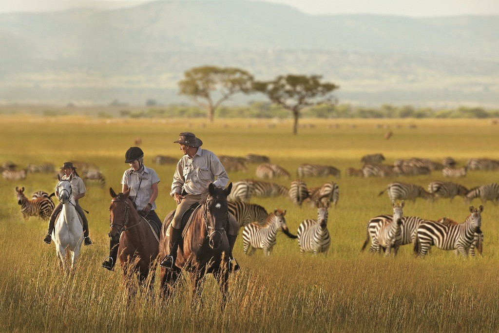 Singita-Grumeti-Tanzania-guide-riders-walking-zebra-herd-1024-682-1024x682