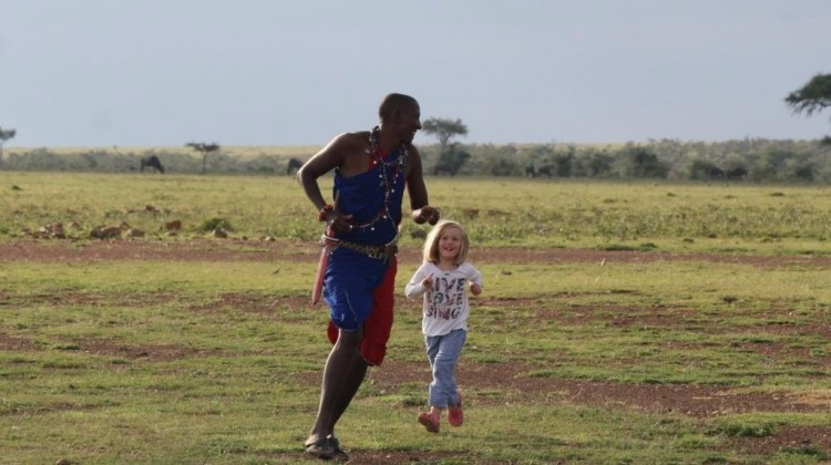 Masai children safari guide educating and entertaining Forbes family children on holiday in the Masai Mara Kenya