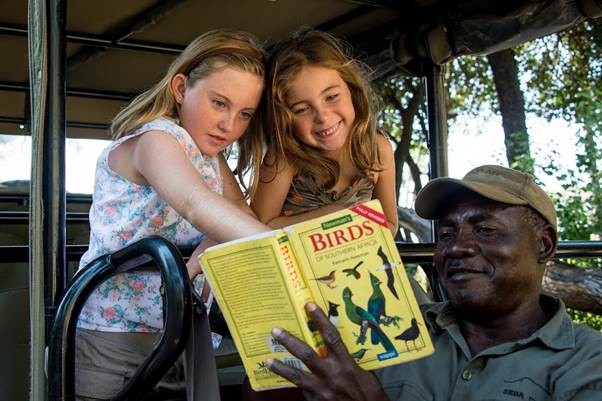 Seba Camp two girls learning about birds with guide Okavango delta Botswana