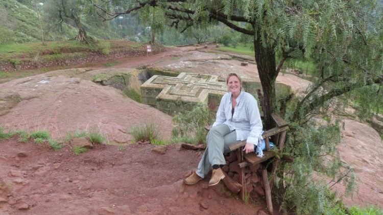 Roxy Cox visiting Ethiopean rock hewn church in Lalibela, Ethiopia, seated under a tree