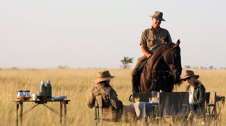 Ride Botswana - botswana riding safaris group on a tea break, picnic table, guide on horseback and guests seated