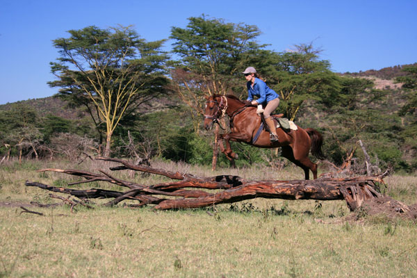 Alice Gully riding a horse jumping a log in Kenya