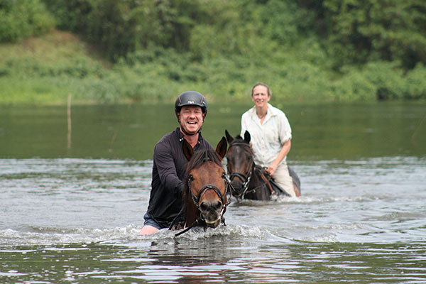 Riding safari in Uganda - horseriding couple swimming with their horses in the Nile