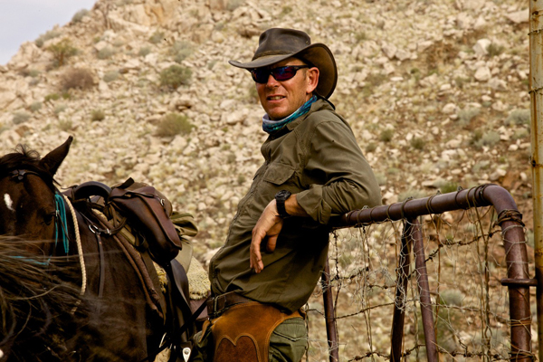 Riding guide Andrew Gillies with horse leaning on a gate, Namibia Horse Safaris