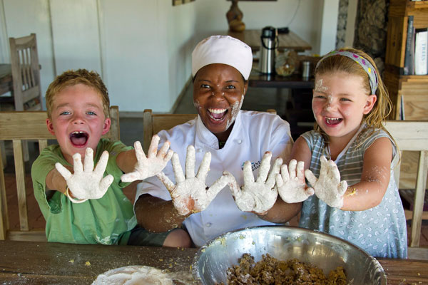Children with messy baking hands at Anderssons Camp Namibia with babysitter