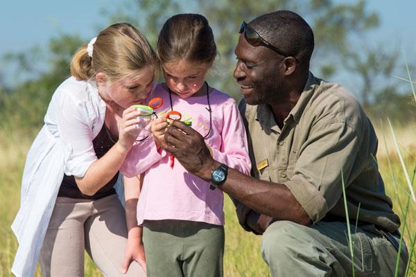 Two girls with magnifying glasses with safari guide, Seba Camp, Okavango Delta, Botswana