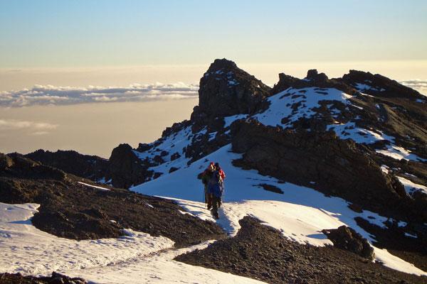 Trekkers nearing the icy summit climbing Mount Kilimanjaro