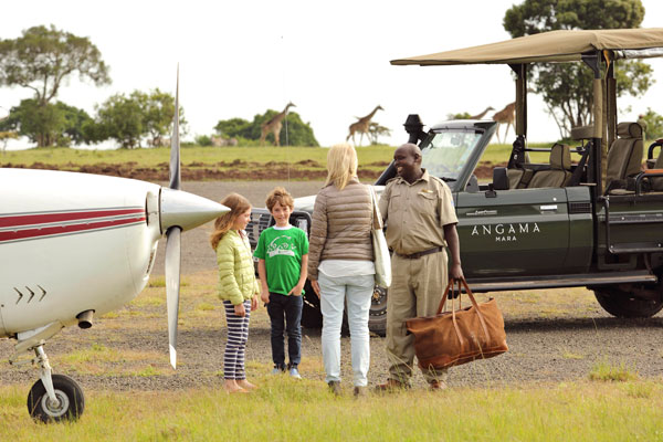 Family arriving on bush plane at Angama Mara Masai Mara Kenya