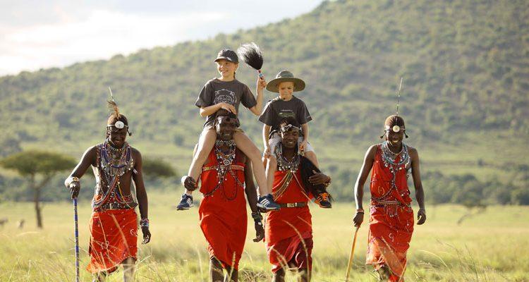 Travelling with children, children on heads and shoulders of Masai, Masai Mara, Kenya AndBeyond Kichwa Tembo