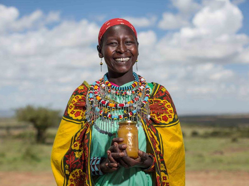 Maa Trust African lady holding jar of honey
