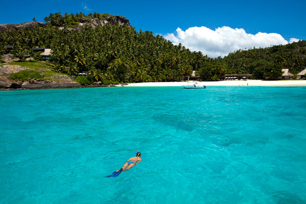 Seychelles outer islands man snorkelling in blue sea with Denis Island beach in background