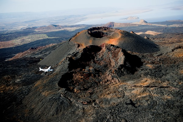 volcanic landscape scattered with dramatic calderas and blackened lava flows