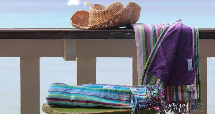 aspiga kikoys folded by the beach and rattan hat