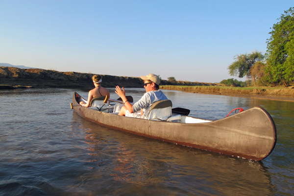 Teenagers canoeing on a tranquil channel of the Chongwe River family safari experiences