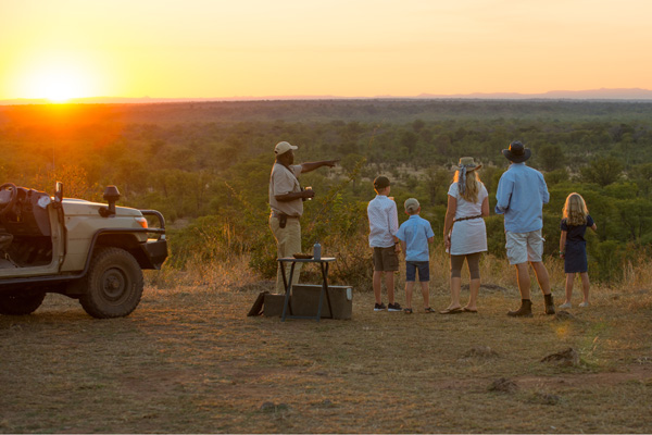 Family watching the sundown with guide after a safari Luangwa Safari House family safari experiences