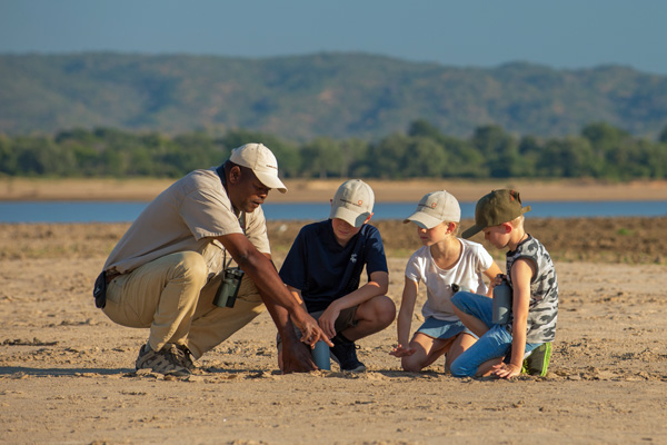 Guide and children looking an tracks and spoor family safari experiences