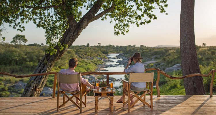 Rekero Camp couple having drinks by the river Mara conservancies