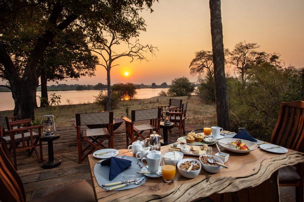 Mpala Jena Camp private dining by the Zambezi at sunset