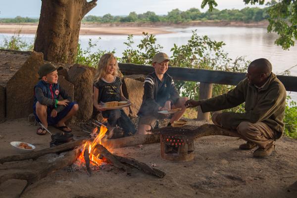 Children enjoying camp fire cooking, Robin's House, South Luangwa, Zambia