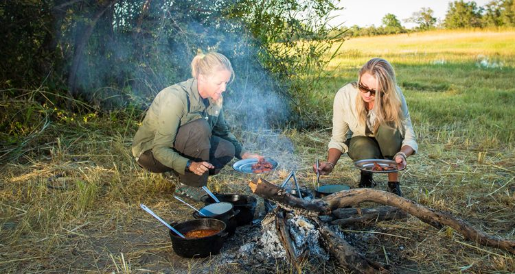 Miracle cooking on safari -ladies cooking around a camp fire in the bush
